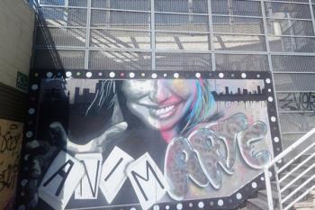 Dos participantes de `Muros Vivos´ dejan sus graffitis en la fachada