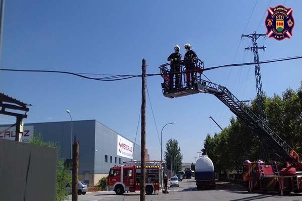 Una grúa se engancha al cable telefónico y tira varios postes en Alcorcón